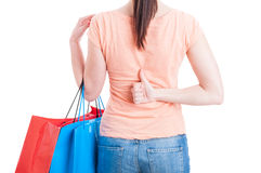 Female holding shopping bags and showing thumb-up behind back Royalty Free Stock Photography
