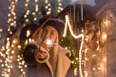 Female holding sparkler against Christmas lights decorated house royalty free stock photo