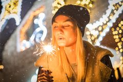 Portrait of young beautiful woman with sparkler in front of Christmas decoration outdoors royalty free stock images