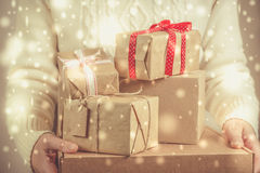 Female holding stack of christmas presents. Christmas concept. Toned, snow effect Royalty Free Stock Images