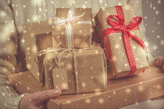 Female holding stack of christmas presents. Christmas concept. Toned, snow effect Stock Photo