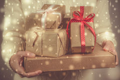 Female holding stack of christmas presents. Christmas concept. Toned, snow effect Royalty Free Stock Photo