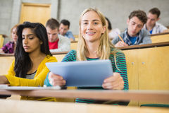 Female holding tablet PC with students at lecture hall Royalty Free Stock Image