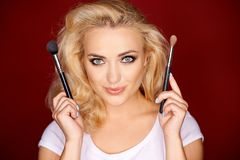 Female holding up makeup brush Royalty Free Stock Photography