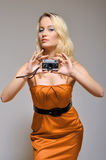 Female holding vintage camera. Young blonde caucasian female with long blond hair holding a vintage camera. She is wearing an orange dress Stock Photo