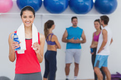 Female holding water bottle with fitness class in background Royalty Free Stock Photos