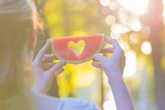 Female holding watermelon with heart shape hole in nature. Summertime concept stock image