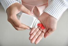 Female holding a white pill bottle and red pills in heart shape. Female is holding a white pill bottle and red pills in heart shape with her hands. Valentines Stock Photography