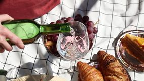 Female holding a wine glasses for a date on checked litter with grape and croissants. stock video