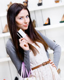 Female holds credit card in footwear shop Royalty Free Stock Photo