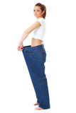 Female holds her old huge jeans, diet concept Royalty Free Stock Photo