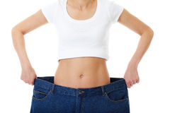Female holds her old huge jeans, diet concept Stock Photo