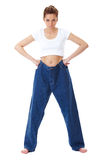 Female holds her old huge jeans, diet concept Royalty Free Stock Images