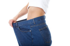 Female holds her old huge jeans, diet concept Royalty Free Stock Photography