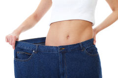Female holds her old huge jeans, diet concept Stock Photos