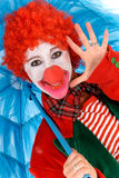 Female holiday clown. Colorful dressed female holiday clown, happy joyful expression on face. Studio shot Royalty Free Stock Photos