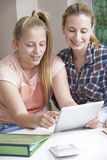 Female Home Tutor Helping Girl With Studies Using Digital Tablet Stock Photo