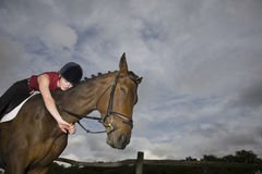 Female Horseback Rider embracing Horse Stock Image