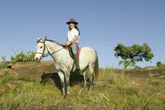 Female horseback rider and horse ride overlooking Lewa Wildlife Conservancy in North Kenya, Africa Stock Images
