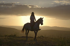 Female horseback rider and horse ride to overlook at Lewa Wildlife Conservancy in North Kenya, Africa at sunset Royalty Free Stock Image