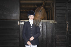 Female Horseback Rider With Horse In Stable. Portrait of a confident female horseback rider with horse in the stable Royalty Free Stock Image