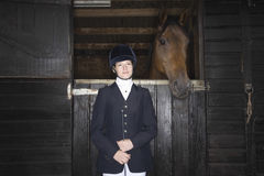Female Horseback Rider With Horse In Stable Stock Photography
