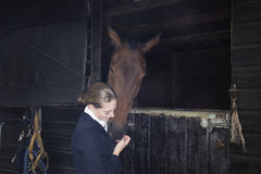 Female Horseback Rider With Horse In Stable Stock Photo