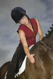 Female Horseback Rider Stroking Horse Royalty Free Stock Image