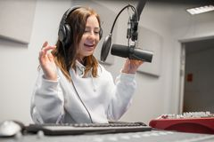 Female host communicating on microphone in radio studio. Happy young female host communicating on microphone in radio studio Royalty Free Stock Photos