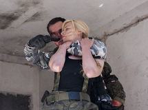Female hostage and hijacker with gun Stock Photography