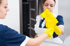 Female hotel maid wiping bathroom mirror Stock Image