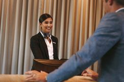 Concierge helping guest with hotel room bookings. Female hotel receptionist attending a guest at reception counter. Happy female concierge helping businessman Stock Images