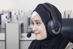 Female hotline operator with headphones. Closeup of pretty Arabian hotline operator with headphones in the office room Stock Photography