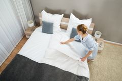 Female housekeeper changing bedding Stock Images