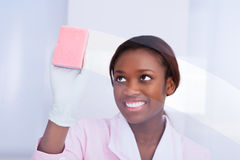 Female Housekeeper Cleaning Glass In Hotel. Happy African American female housekeeper cleaning glass in hotel Stock Images