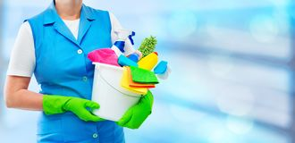 Female cleaner holding a bucket with cleaning supplies. Female housekeeper while cleaning office. Woman wearing protective gloves and holding bucket full of stock photography