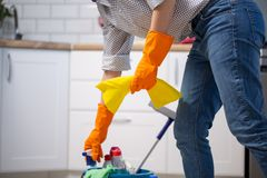 Female housekeeper while cleaning office. Woman wearing protective gloves near bucket full of cleaning supplies stock photos