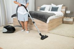 Female housekeeper cleaning with vacuum cleaner Royalty Free Stock Photos
