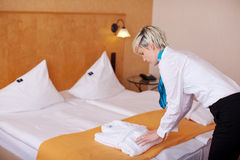 Female Housekeeper Keeping Bathrobe On Bed. Side view of young female housekeeper keeping bathrobe on bed in hotel Stock Photography