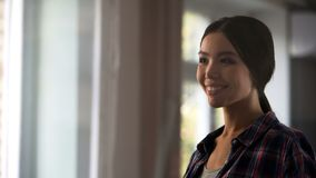 Female housekeeper looking satisfied at room window after cleaning, hygiene. Stock footage Royalty Free Stock Photography