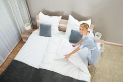 Female housekeeper making bed with bed clothes Royalty Free Stock Image