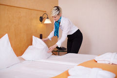 Female Housekeeper Making Bed In Hotel Room Royalty Free Stock Photos