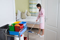 Female Housekeeper Mopping Floor. Happy Female Housekeeper Mopping Floor In Hotel Room Royalty Free Stock Images