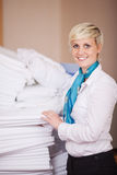 Female Housekeeper Stacking Sheets In Stock Room. Portrait of young female housekeeper stacking sheets in stock room Stock Photo