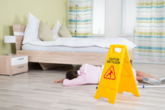Female Housekeeper Unconscious Near Wet Floor Sign. Young Female Housekeeper Unconscious Near Wet Floor Sign In Hotel Room Royalty Free Stock Photos