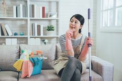 Female housekeeper wearing apron sitting on couch. Resting with a bucket full of cleaning products after mopping the floor in the living room. young housewife royalty free stock image