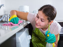 Female houseworker with rag and cleanser indoors. Portrait of young spanish female houseworker with rag and cleanser indoors Stock Photos