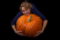 Female with a huge pumpkin. Female hugging a huge pumpkin Royalty Free Stock Image