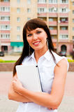 Female hugging a netbook. Beautiful woman in the background of the building Stock Image