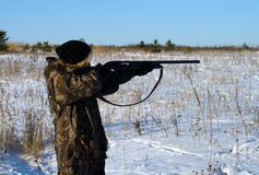 The female hunter. Girl shoots from a hunting rifle in the winter field Stock Image